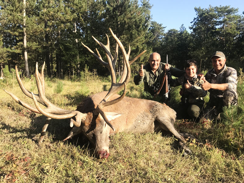 Hunter with a big red stag trophy in France