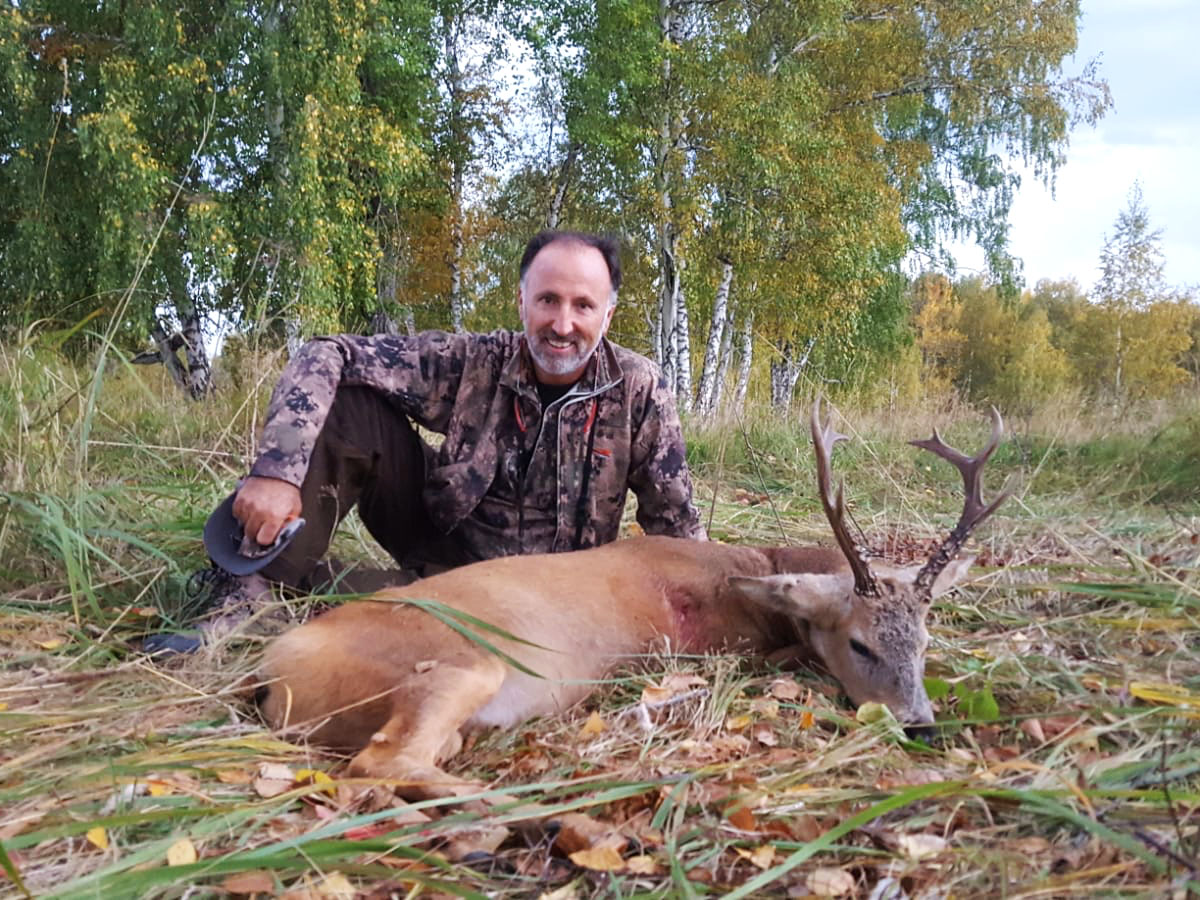 Hunter with a siberian roebuck in Russia